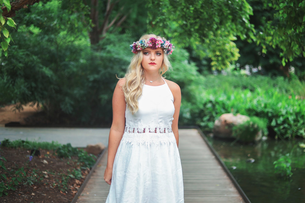 Senior girl wearing white dress and flower head band standing on bridge at Myriad Gardens in Oklahoma City