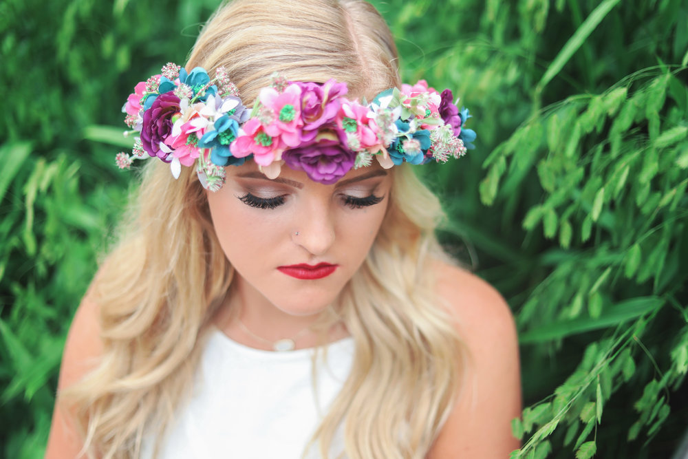 Senior girl wearing flower head band looking down