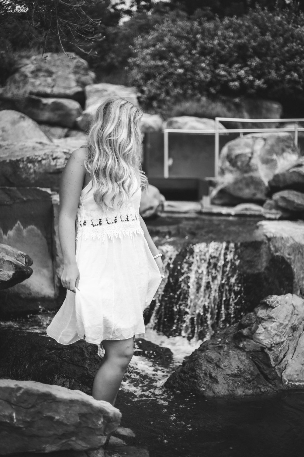 black and white photo of high school senior girl wearing a white dress standing in a fountain at Myriad Gardens in Oklahoma City.