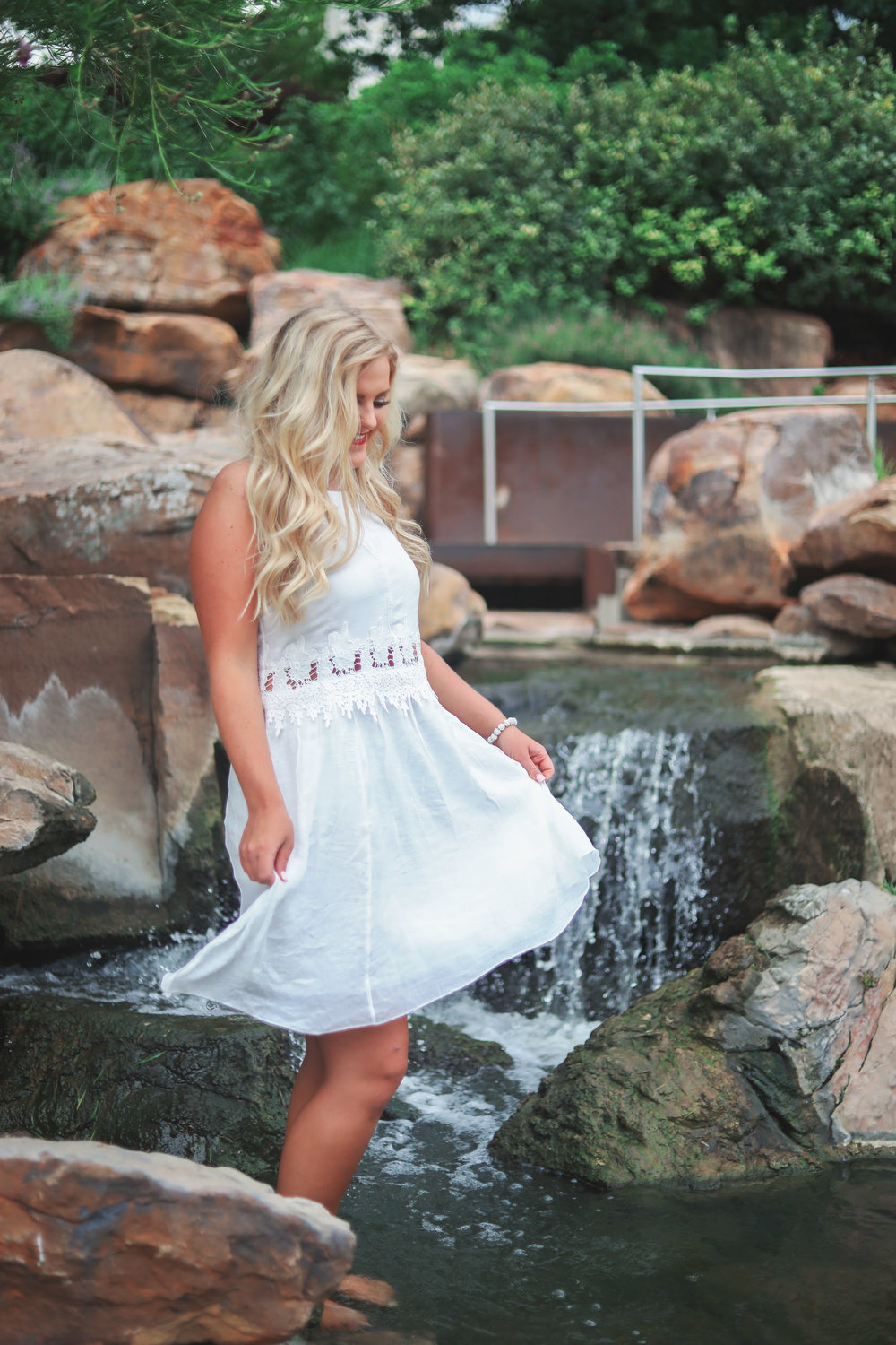 High School Senior girl wearing white dress standing barefoot in a fountain at Myriad Gardens in Oklahoma City.