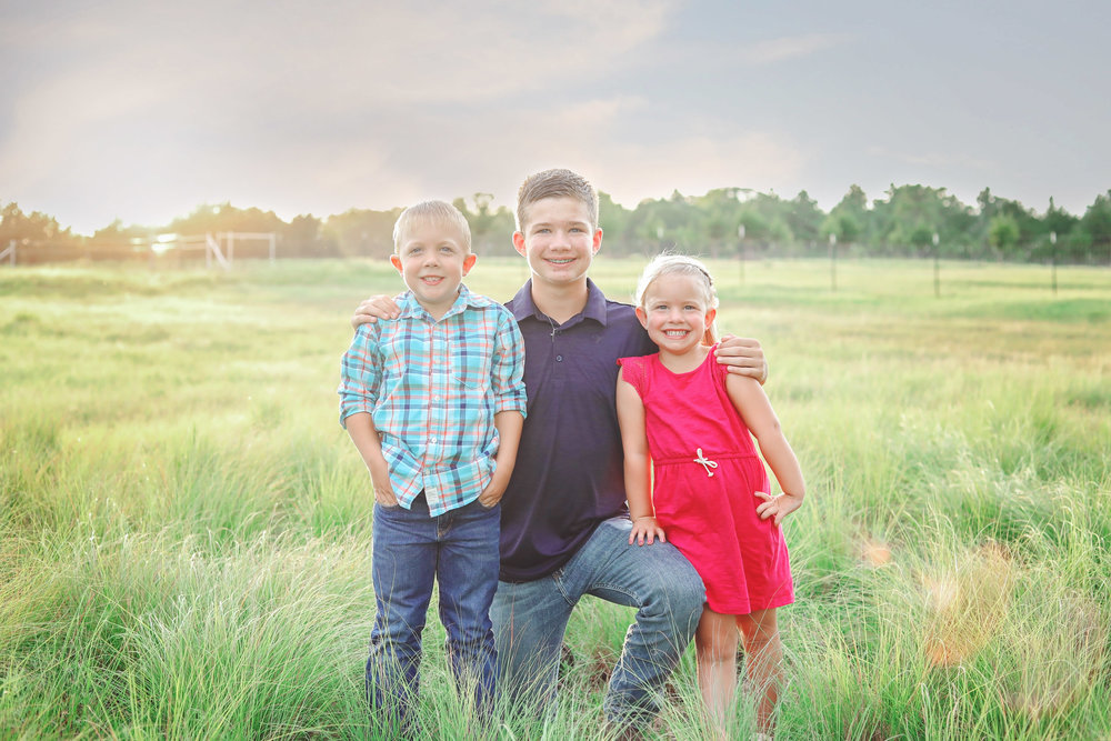 three siblings wearing blue and pink in a field in stillwater Oklahoma