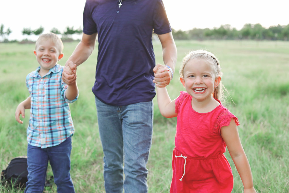 Three siblings walking through a pasture, close up on little girls face.