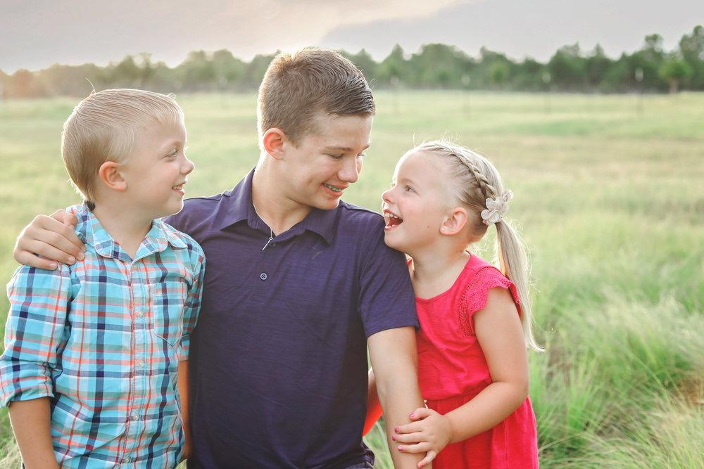 Three siblings sitting in pasture in Stillwater, Oklahoma.