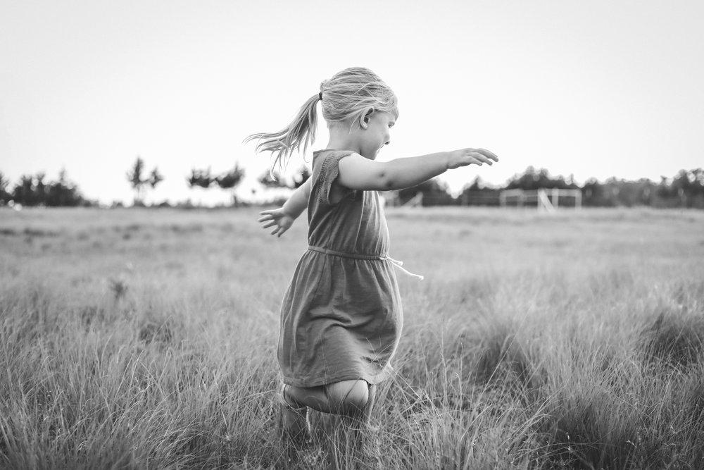 Black and white of little girl twirling in a field in Stillwater, Oklahoma.