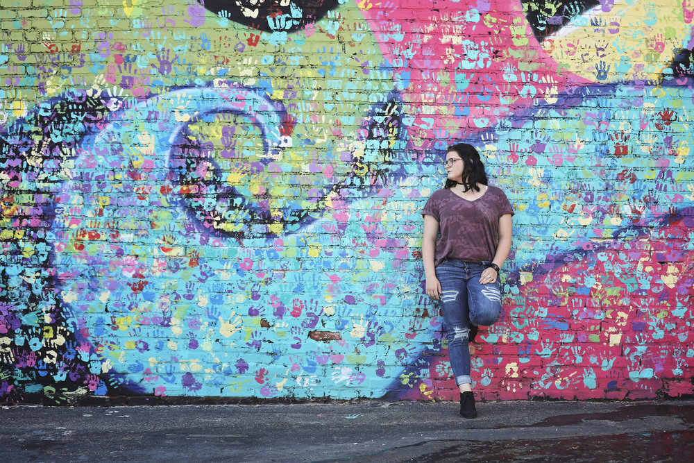 High school senior girl wearing jeans and glasses leaning against a graffiti wall in downtown Tulsa.