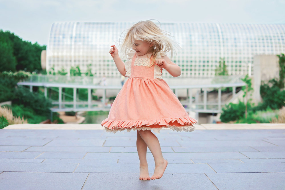 Little girl wearing pink dress dancing  at the Myriad Gardens in Oklahoma City.
