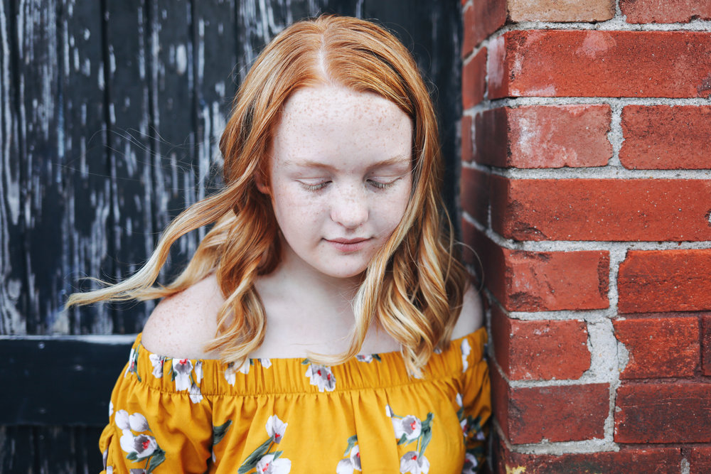 Close up photo of teenage girl with red hair leaning on brick wall in downtown OKC.