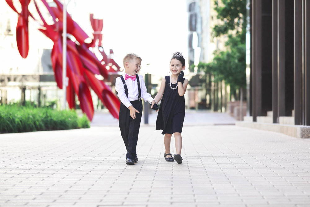 Little boy wearing a suit and bow tie and little girl dressed like Audrey Hepburn walking down the sidewalk in downtown Oklahoma City.