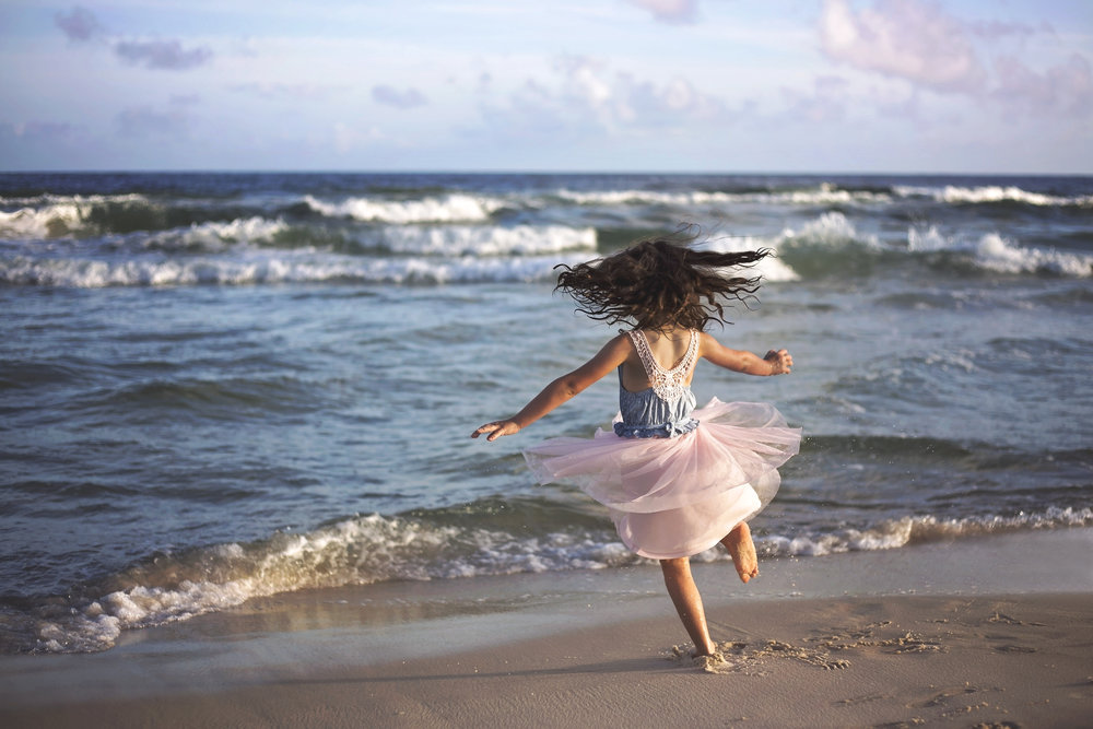 Color image of little girl wearing pink dress dancing on the waters edge at Orange Beach, Alabama.