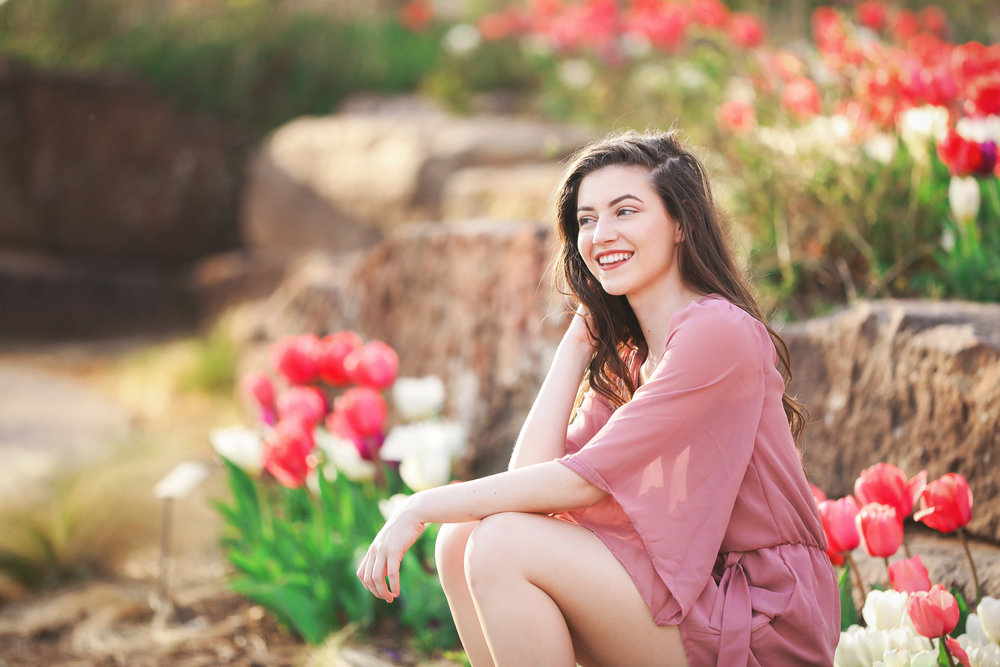 High school senior girl wearing pink outfit sitting on a rock surrounded by tulips at the Myriad Gardens in Oklahoma City.