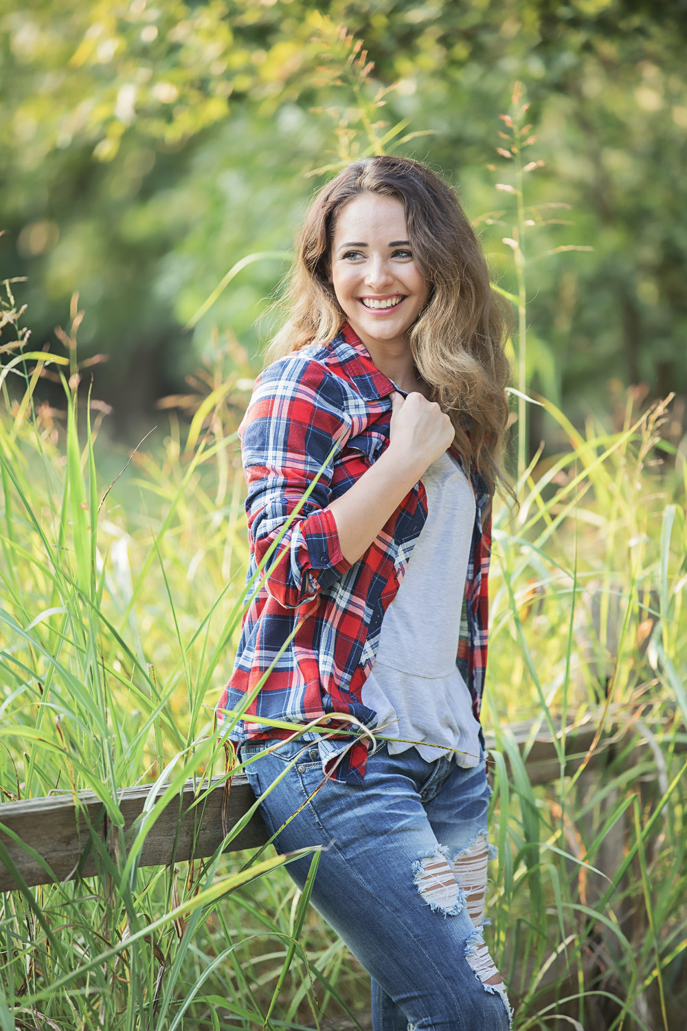 Senior girl wearing flannel, holding collar and looking to the side, leaning against wooden rail at park in Oklahoma City.  Amanda Lynn Photography
