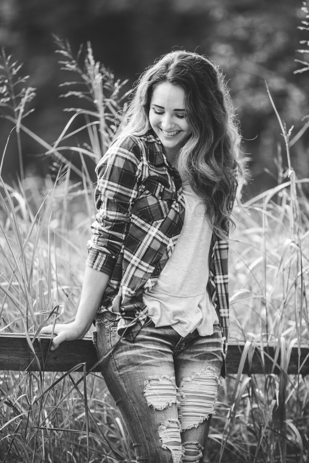 Black and white photo of high school girl laughing at a park in Oklahoma.  Oklahoma City Photographer.