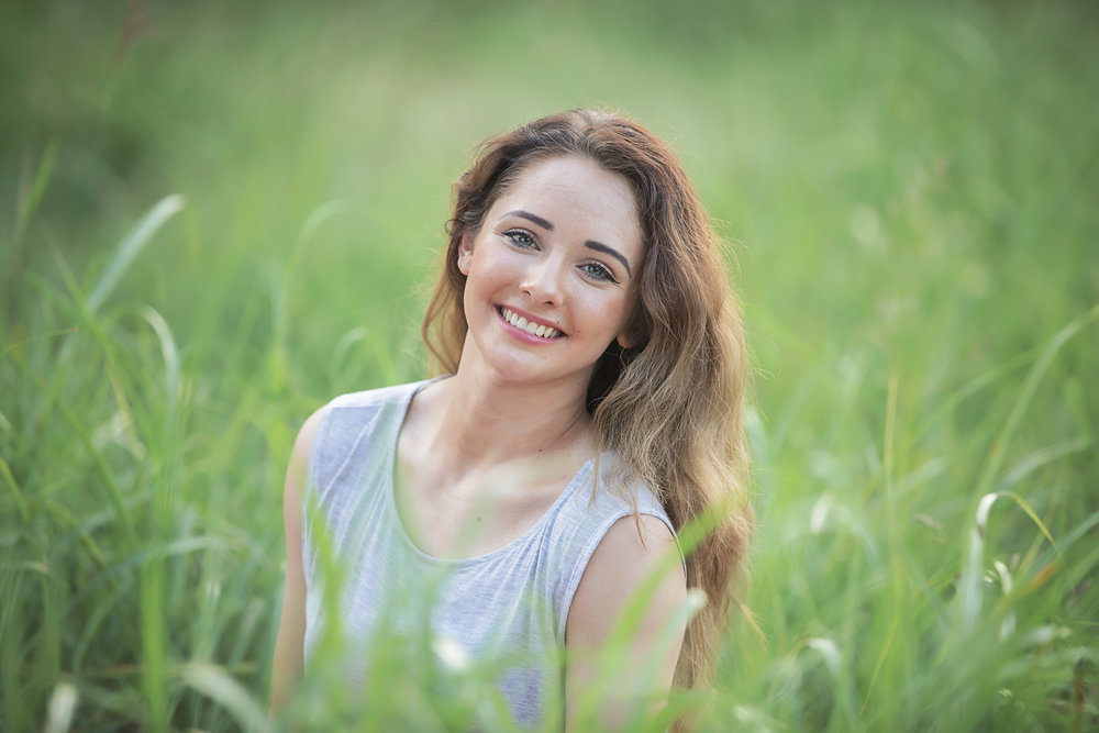 Close up of senior girl wearing gray tank top sitting in tall grass in an open field in Oklahoma City.