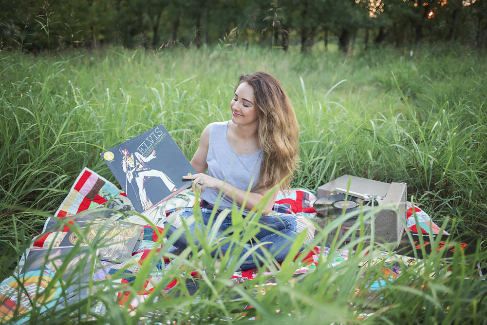 Senior girl sitting on a red quilt surrounded by old records and a record player, holding an Elvis album.  Oklahoma City Senior Photographer Amanda Lynn.