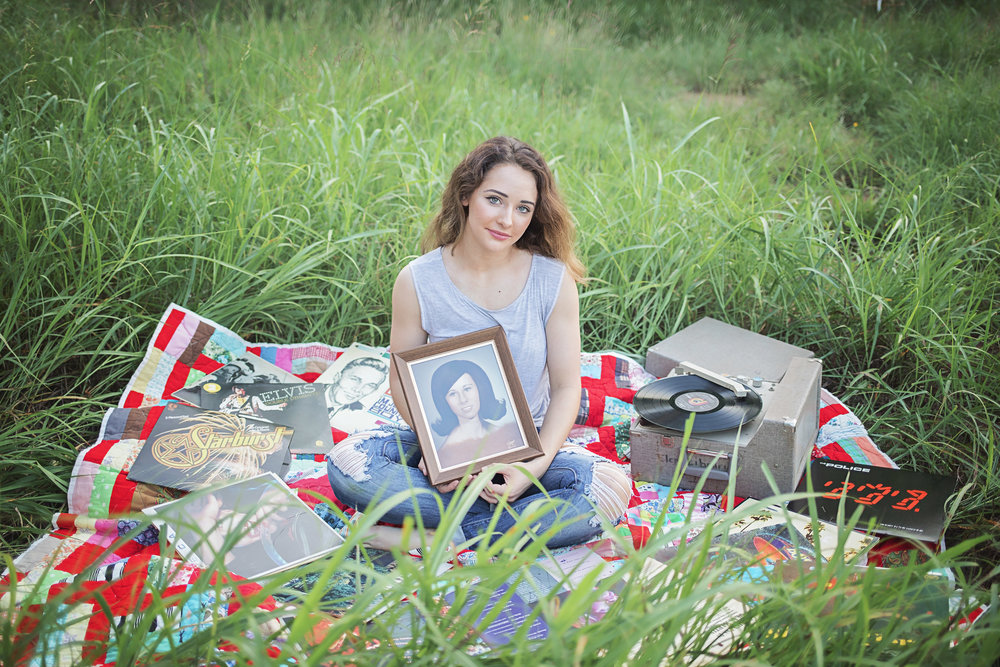 Senior girl paying tribute to her late grandmother by holding grandmothers high school senior photo.