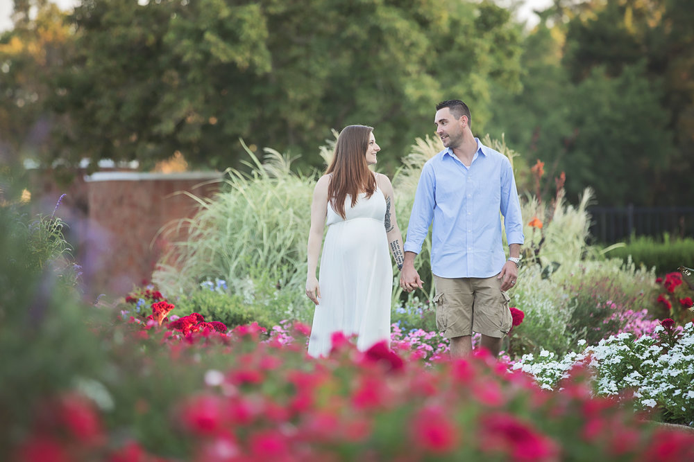 Husband and wife holding hands and walking surrounded by flowers at maternity photoshoot at Will Rogers Park in Oklahoma City.
