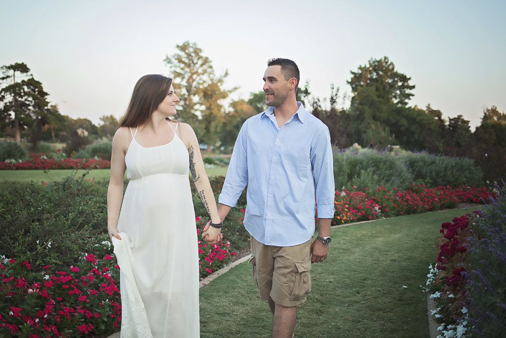 Husband and wife holding hands and walking in park during maternity photoshoot in OKC.