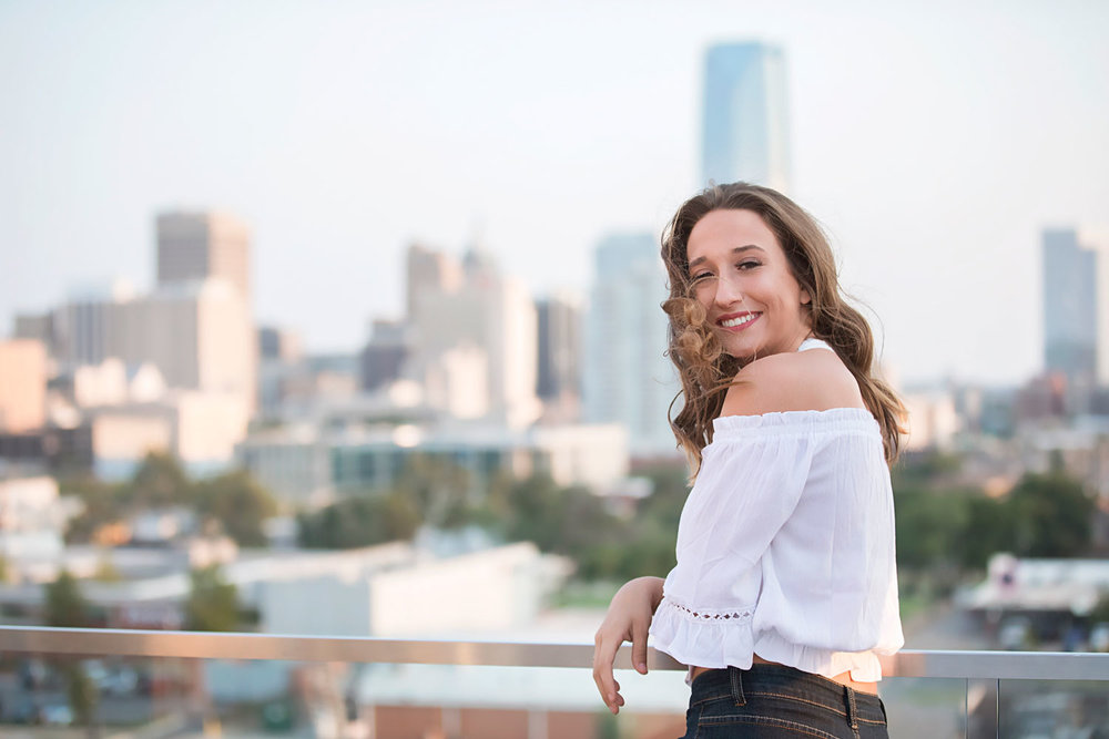 Image of senior girl wearing white shirt looking over shoulder with hair in face and downtown Oklahoma City behind her.