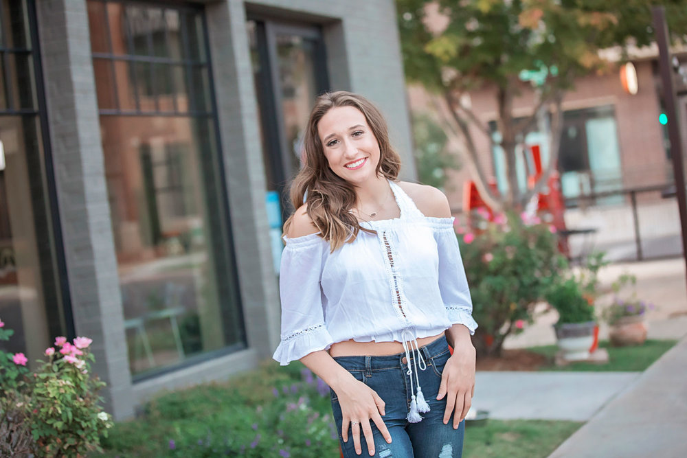 Senior girl wearing white shirt and blue jeans standing and smiling at camera.  Oklahoma City Senior Photographer Amanda Lynn.