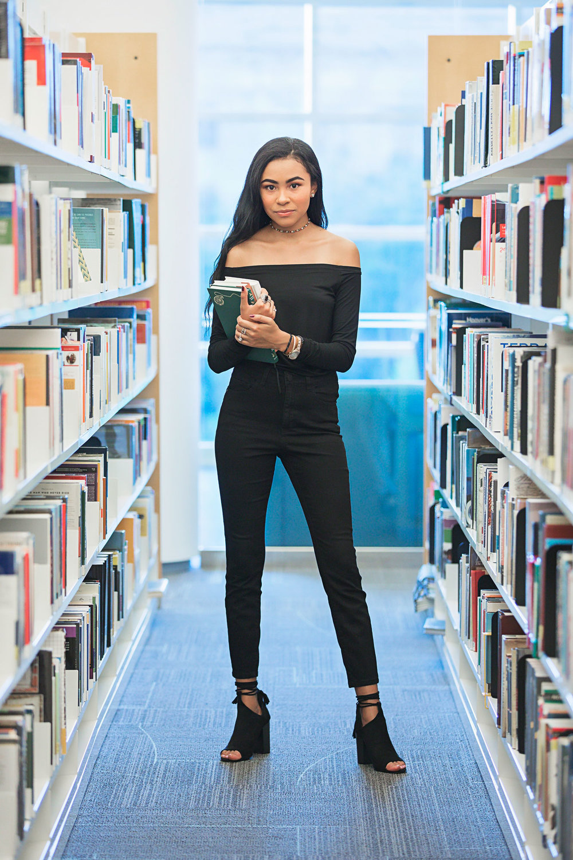Oklahoma senior girl wearing all black and holding books at the OKC downtown Metropolitan Library. Amanda Lynn Oklahoma City Photographer.