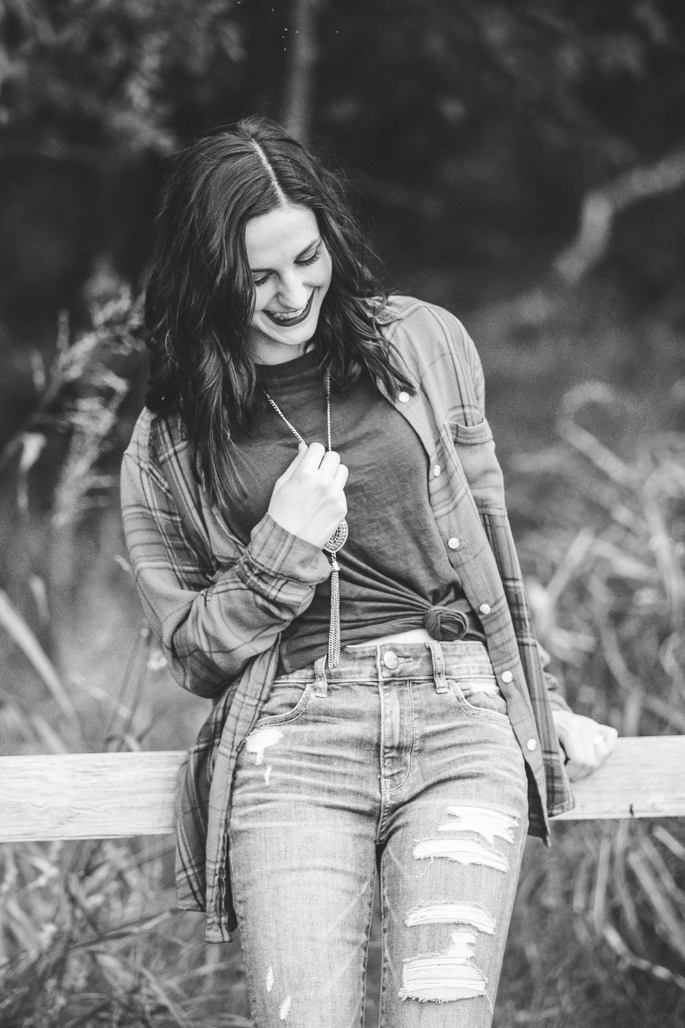 Black and white image of high school senior girl leaning against wooden fence at Martin Park Nature Center in Oklahoma City. By Amanda Lynn Photography.