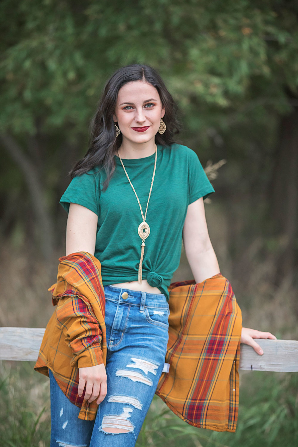 Image of senior girl with long brown hair, wearing green t-shirt with mustard yellow flannel, leaning against wooden fence at a park in Oklahoma City by Amanda Lynn Photography.