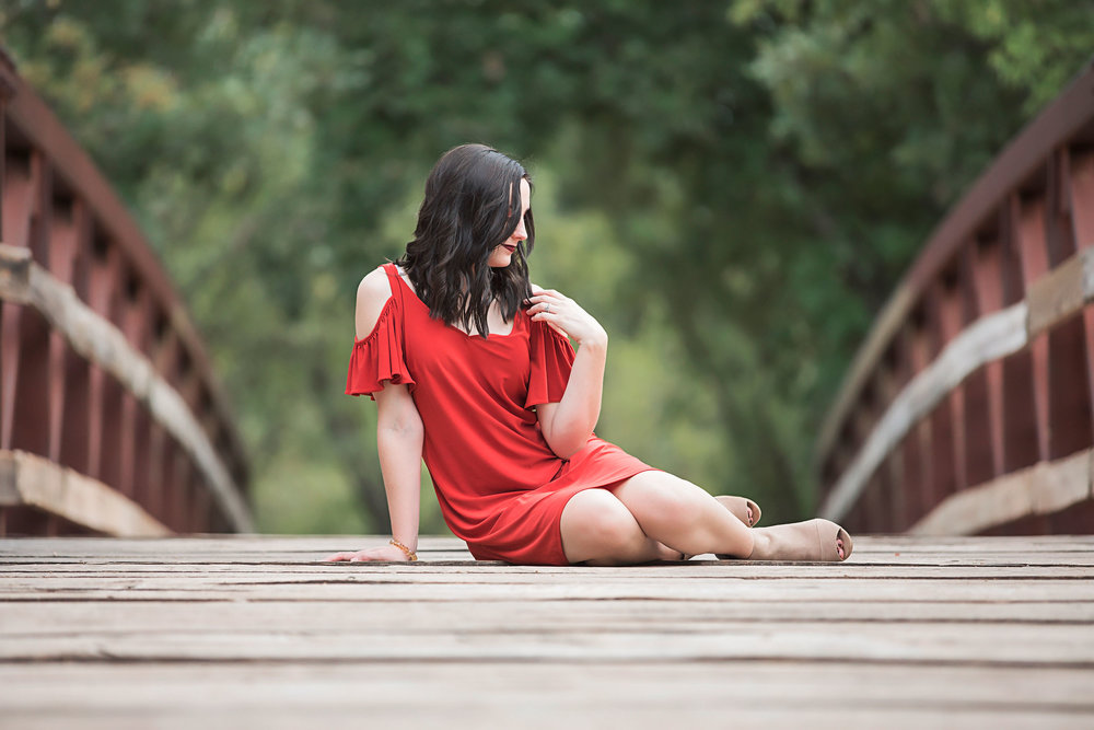 Senior girl with long brown hair, wearing orange dress and sitting on a wooden bridge at Martin Park Nature Center in Oklahoma City.