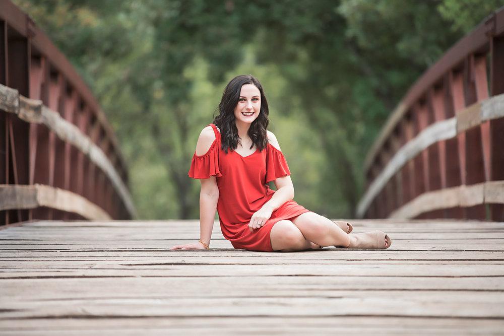 High School Senior girl wearing orange dress sitting on wooden bridge at park in OKC, by Amanda Lynn Photography.