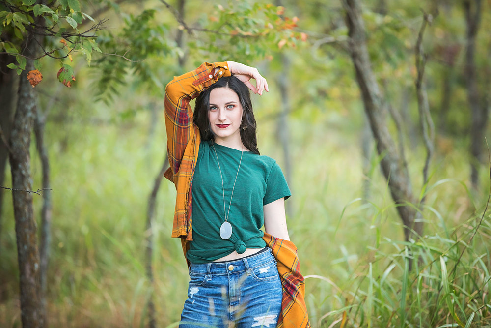 High School senior girl wearing green shirt and yellow flannel standing in woods with her hands on her head looking towards the camera at Martin Nature Park in Oklahoma City.