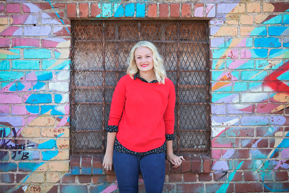 Senior high school girl wearing orange sweater, leaning against graffiti wall in downtown Oklahoma City by Amanda Lynn.