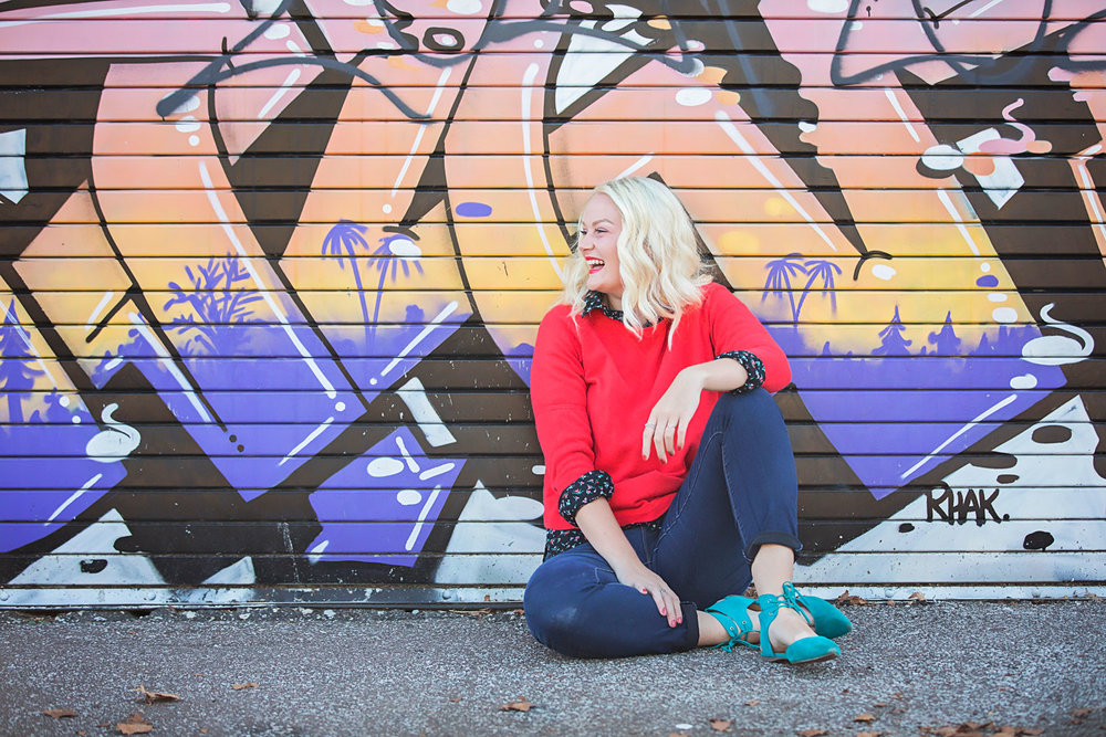 Senior girl with blonde hair, wearing orange sweater and blue shoes, sitting on ground and leaning against graffiti wall in Oklahoma City.