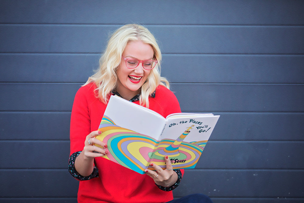 Senior girl wearing red glasses and orange sweater reading Dr. Seuss book in downtown Oklahoma City.