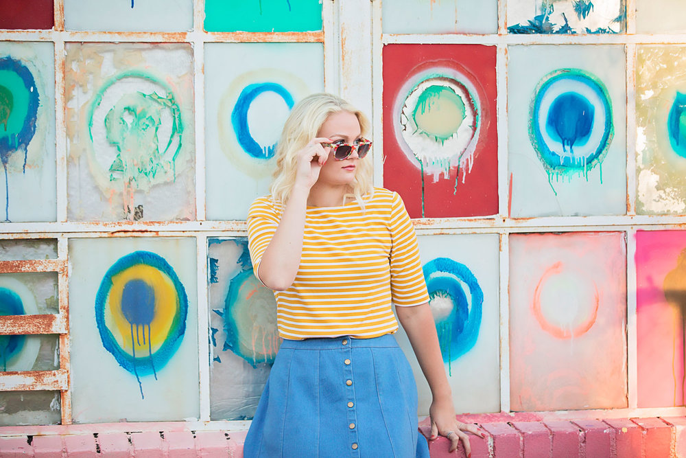 Senior girl wearing yellow shirt and a blue jean dress at the graffiti walls in Automobile Alley Oklahoma City, by Amanda Lynn.