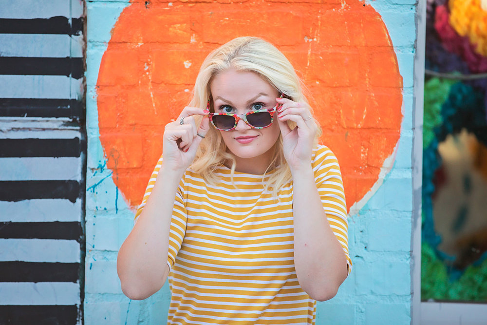 High School Senior girl wearing yellow stripe shirt, standing in front of graffiti wall and looking over sun glasses towards camera in Oklahoma City, Oklahoma.