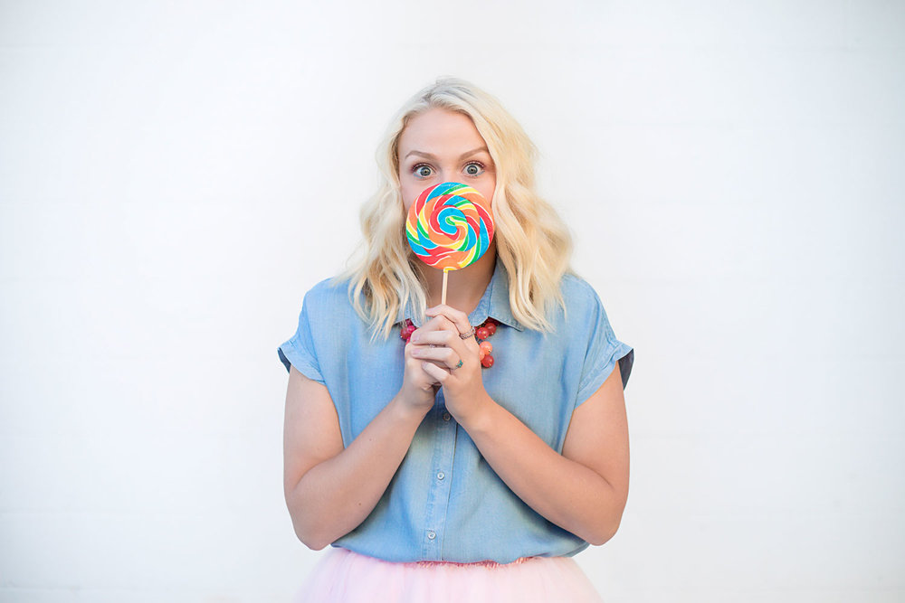 Senior girl holding a colorful lollipop in front of her face in Oklahoma City.