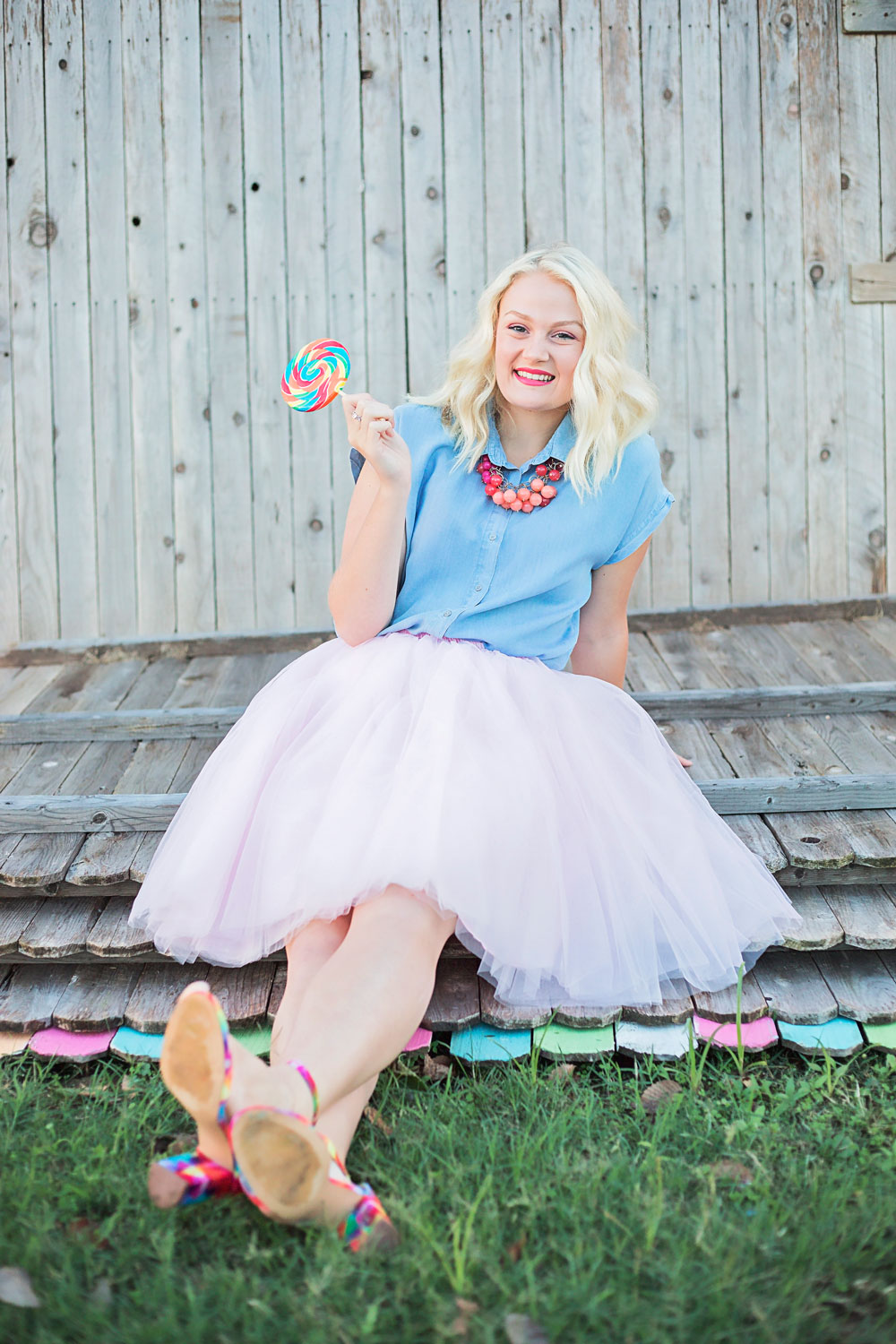 Senior girl wearing pink skirt, sitting on fence panels and eating lollipop by Amanda Lynn in Oklahoma City.