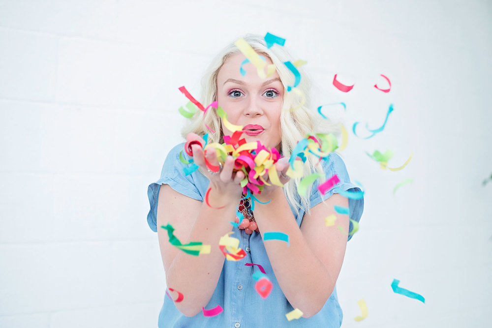 Senior girl blowing colorful confetti by Amanda Lynn Photography in Oklahoma City.