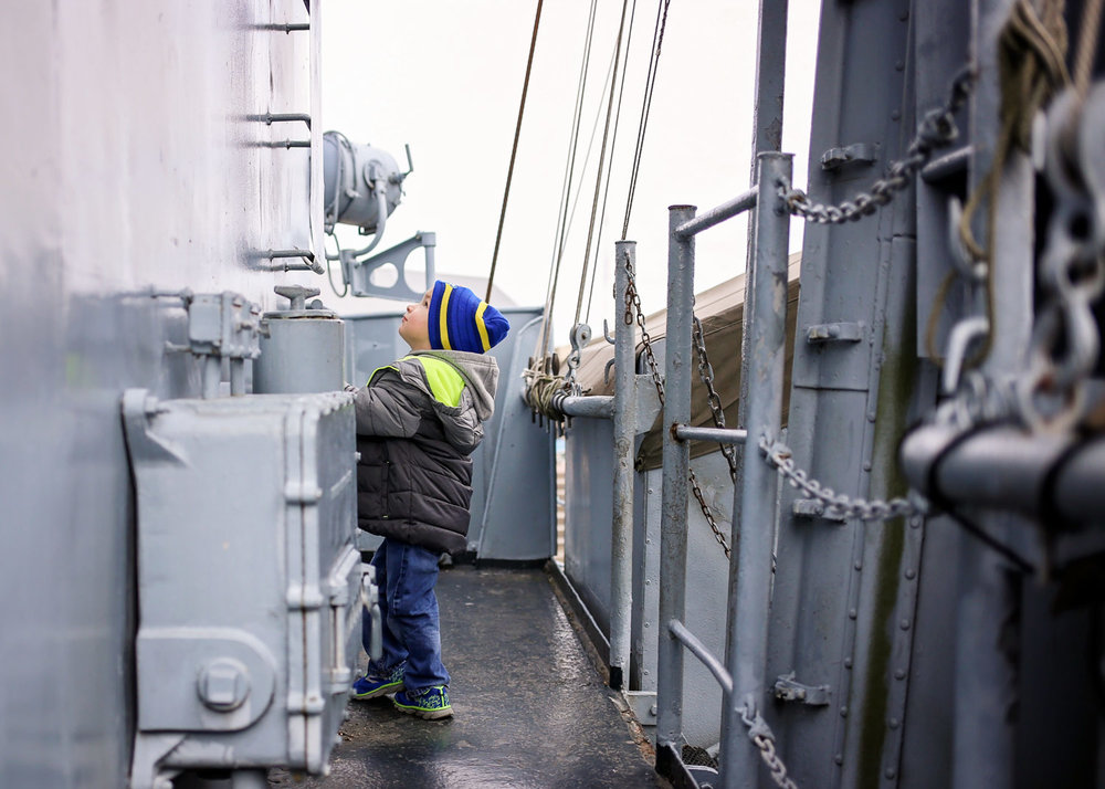 Little boy wearing coat and hat, standing on the USS Kidd in Baton Rouge.