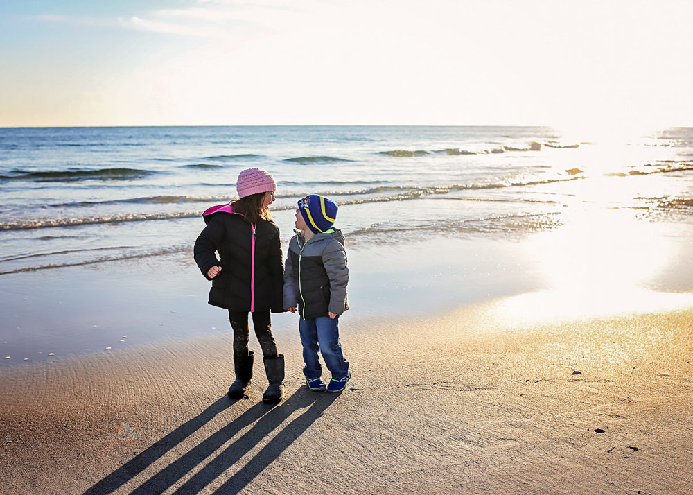 Siblings wearing coats, standing on the beach looking at each other in Orange Beach, Alabama.