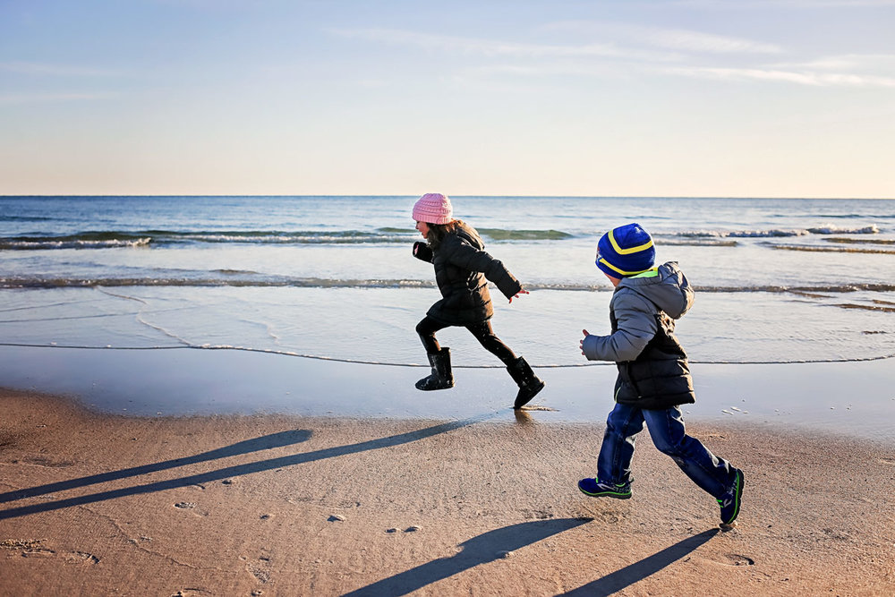 Kids wearing coats and stalking caps, running on the beach in Orange Beach, Alabama.