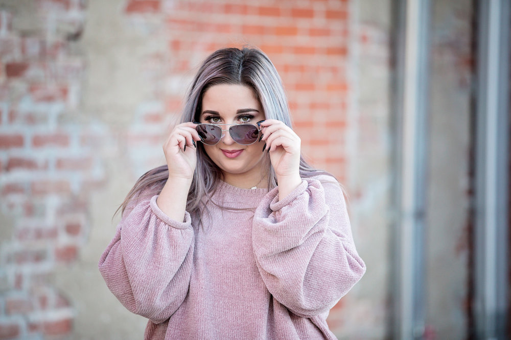 High school senior girl wearing purple sweater, looking at camera over sunglasses while standing in an alley in Oklahoma City.