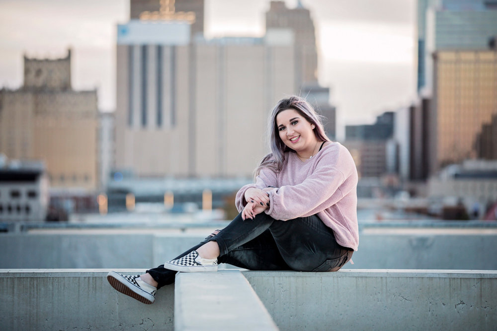 Girl with purple hair, wearing a purple shirt and black jeans, sitting on top of parking garage with downtown Oklahoma City behind her.