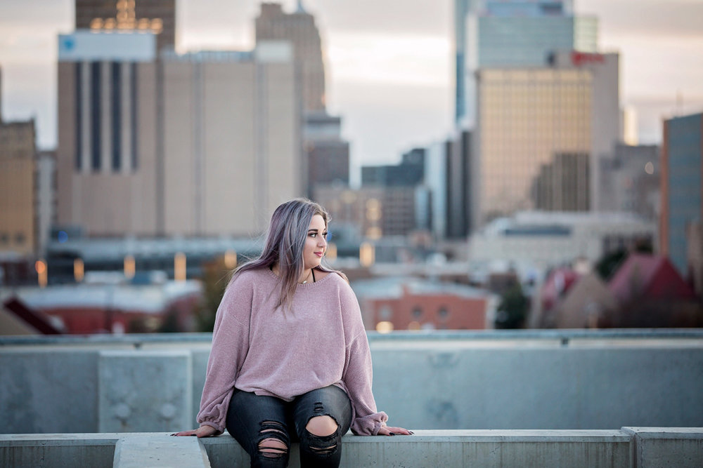 High School Senior sitting on top of parking garage with downtown Oklahoma City in the background by Amanda Lynn.