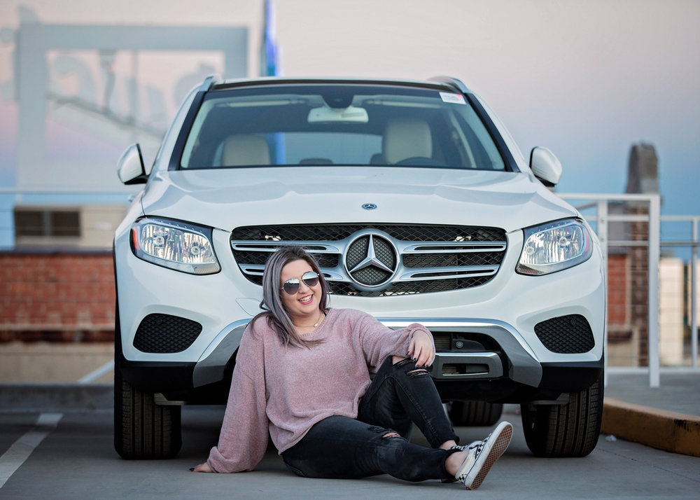 High School senior wearing sunglasses and purple shirt sitting in front of a Mercedes-Benz in Oklahoma City.