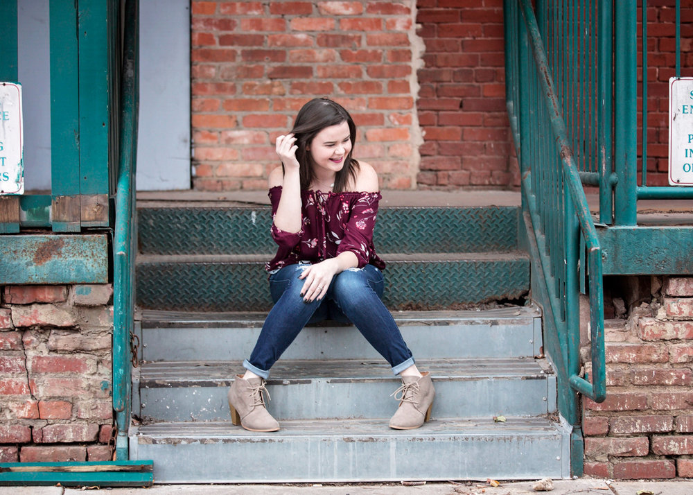 Senior girl, pulling hair behind ear, sitting on greet stair in downtown Oklahoma City.