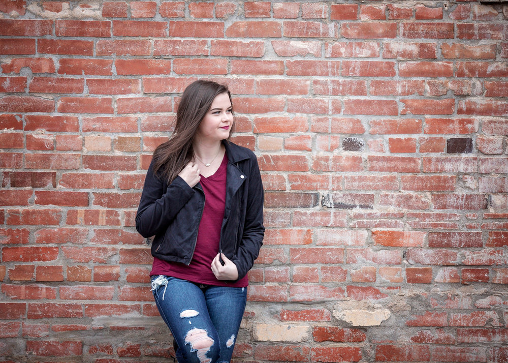 Senior girl wearing jeans and black jacket, leaning against brick wall in Oklahoma.