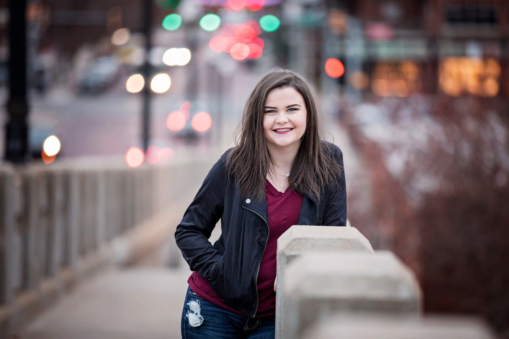 Senior girl leaning against concrete bridge with city lights behind her in Oklahoma City, by Amanda Lynn.