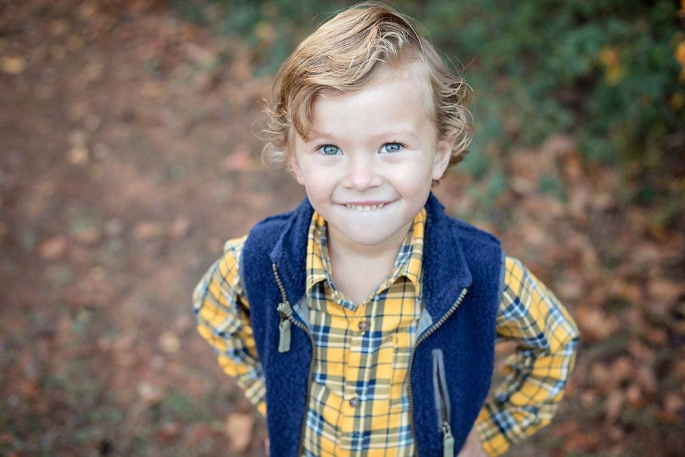 Little boy wearing yellow shirt with blue vest looking up at camera.  Oklahoma City Photographer, Amanda Lynn.
