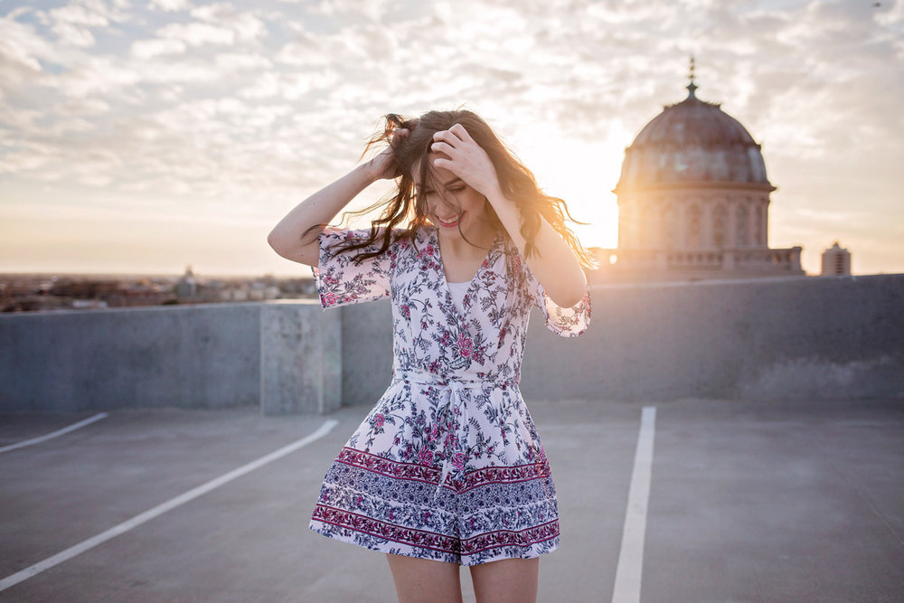 High school senior girl dancing on a rooftop with sun setting behind her in downtown Oklahoma City by Amanda Lynn Photography.