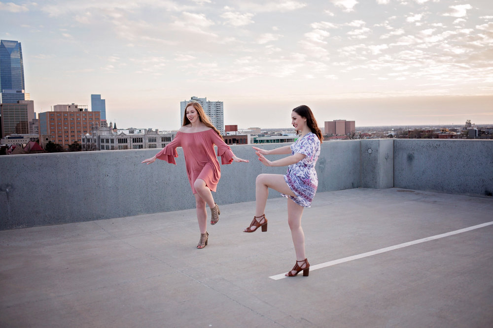 High school senior girls standing on one foot on rooftop in Oklahoma City.